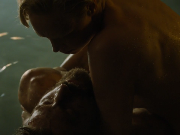 Brienne is covered in water droplets; she holds Jaime in her arms just above the water's surface.